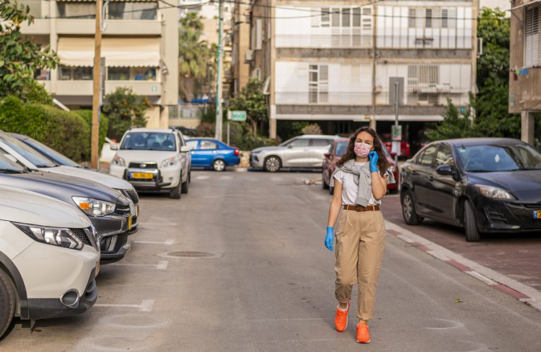Urban View. A Girl In Protective Gloves Walks Along The Street A